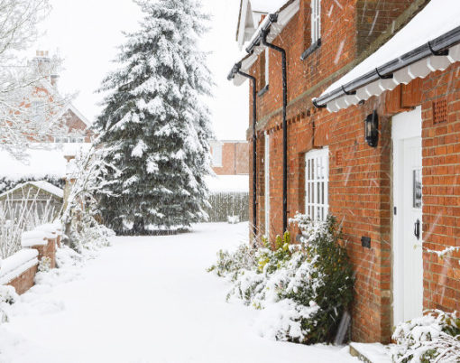 English country home in winter with a driveway covered in snow