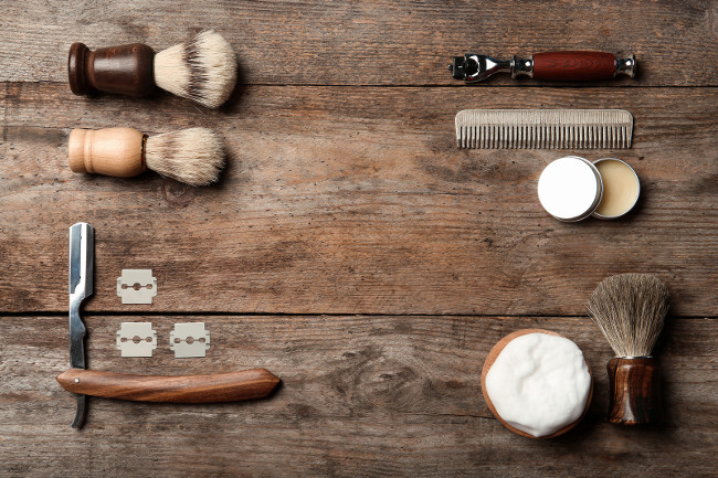 Flat lay composition with men's shaving accessories and space for text on wooden background