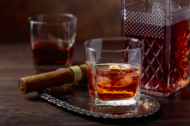 Glass of whiskey with natural ice and cigar on old wooden table.