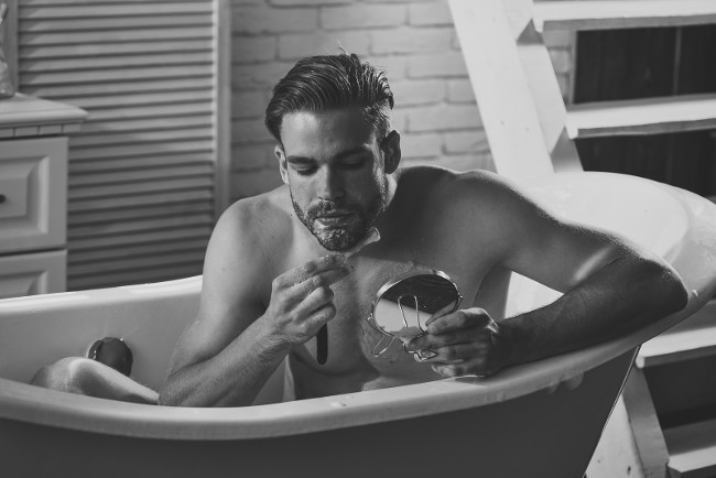 Grooming, hygiene, health. Bearded man shave with razor in bath in bathroom. Shaving, barber, barbershop. Macho with shaving soap on beard hair look in mirror. Skincare, treatment, therapy.
