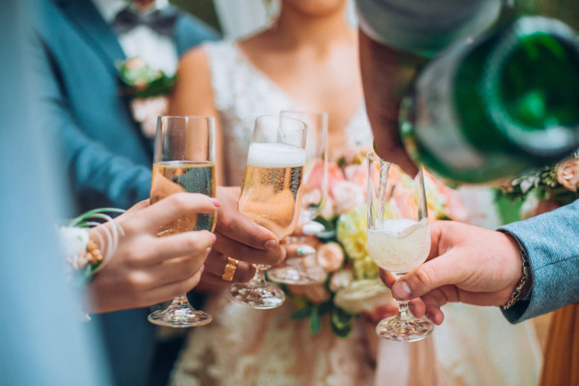 Groomsman opens a bottle of champagne before newlyweds standing in the park. Wedding party in the forest. Bride and groom with friends drink champagne n the park. Funny wedding moments. Crazy people.