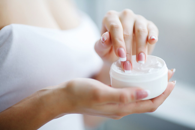 Hand Skin Care. Close Up Of Female Hands Holding Cream Tube, Beautiful Woman Hands With Natural Manicure Nails Applying Cosmetic Hand Cream On Soft Silky Healthy Skin.