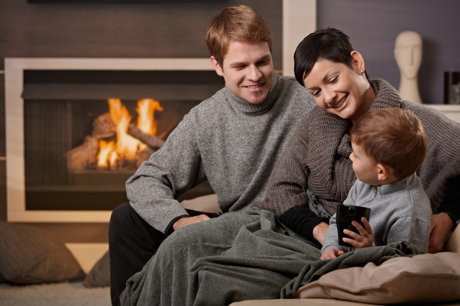 Happy family sitting on couch at home in front of fireplace smiling.