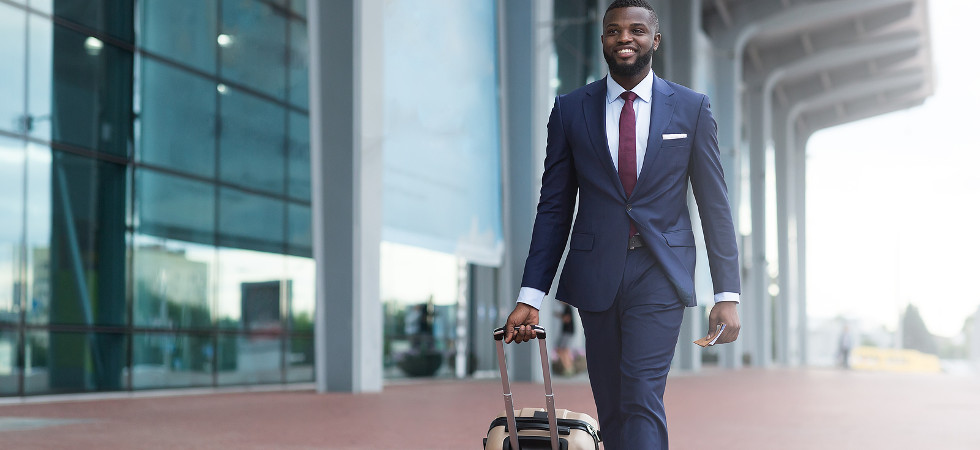 Happy smiling african man in suit with luggage leaving airport.