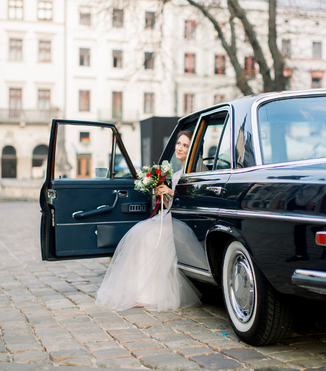 Pretty bride with wedding bouquet in luxury wedding dress sitting in the retro car, parked in old city center