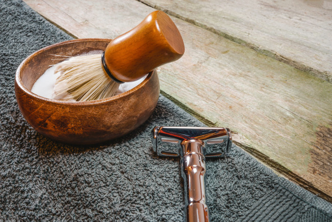 Shiny safety razor, shaving brush and lather in bowl. Old-school wet shaving in rustic wooden table, with copy space.