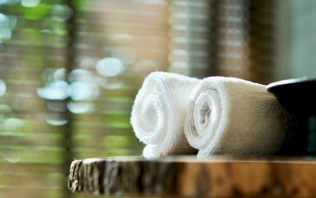 Spa resort composition- wooden plate and towel, place for relaxation in modern wellness center, Warm atmosphere in spa resort, Close up of spa essentials and towels on wooden tray in bathroom, essential oil. Spa products set conception.
