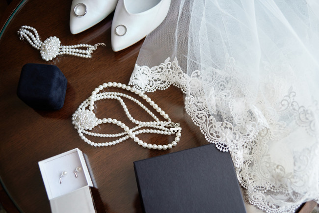 Top view of luxury bridal accessories. Veil, white shoes, golden wedding rings and bride jewelry (pearls necklace, bracelet and earrings) on wooden table, copy space. Wedding morning. Marriage concept