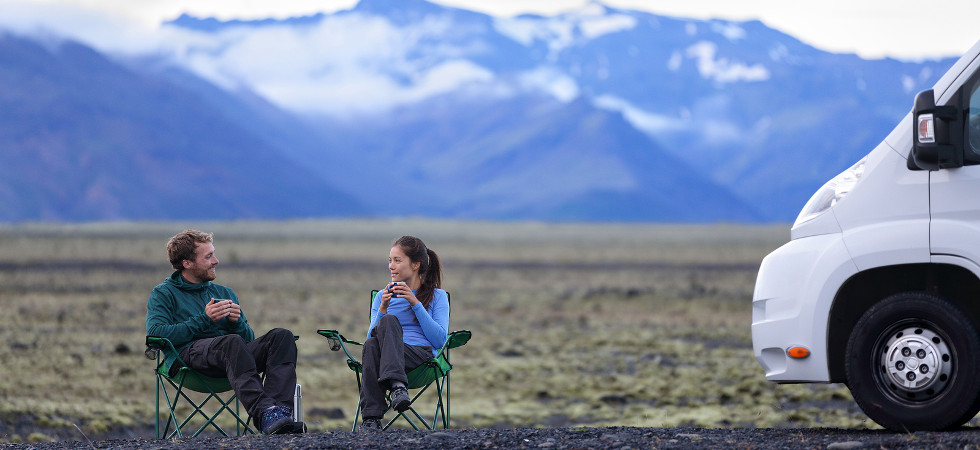 Travel couple by mobile motor home RV campervan. People sitting in chairs relaxing camping and enjoying traveling on Iceland in recreational vehicle. Young couple enjoying coffee in nature landscape.