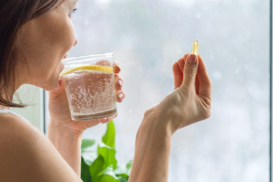 Woman takes pill with omega-3 and holding a glass of fresh water with lemon. Picture of the house, in the morning near the window. Vitamin D, E, a fish oil capsules. Nutrition, healthy eating, lifestyle