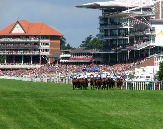 Horse racing at York race course showing riders nearing finishing post.