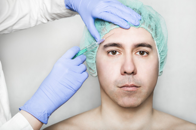 Doctor aesthetician makes hyaluronic acid rejuvenation beauty injections in the forehead of male patient in a green medical cap