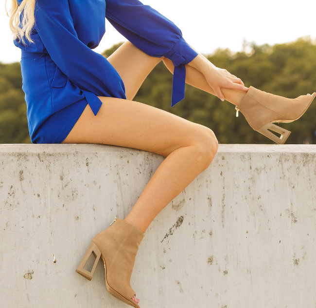 Beautiful unrecognizable woman with long legs wearing suede boots, brown beige high heels shoes