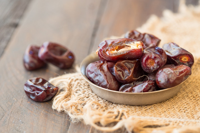 dried fruits (date palm fruits . fresh dates whole and half on wood background