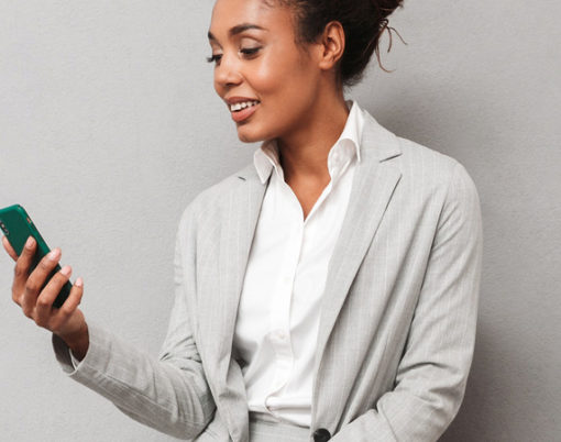 Full length portrait of a confident african business woman wearing suit sitting on a chair over gray background, holding takeaway coffee, using mobile phone