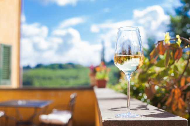 Glass of chilled white wine on a Tuscany background. Agriturismo vacation in Italy