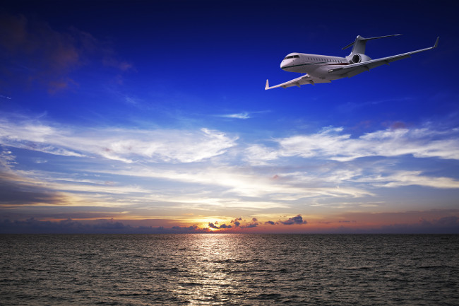 Luxury private jet over the sea at sunset time