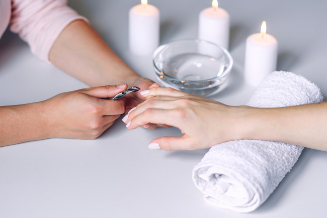Nails beauty. Woman hands receiving nail care treatment by professional manicure specialist in nail salon. Manicurist cutting cuticle on nails with nail clippers
