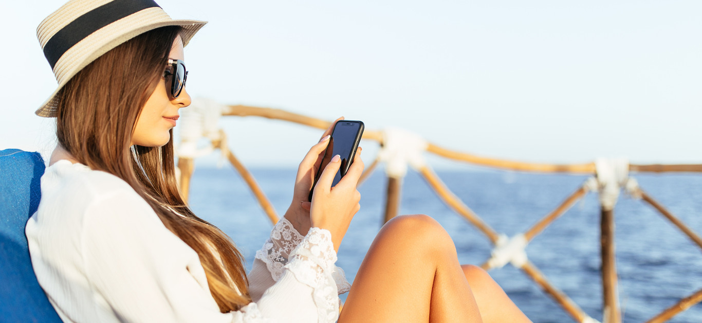 Portrait of young woman lying on a sunbed with phone in the hands on a sea background