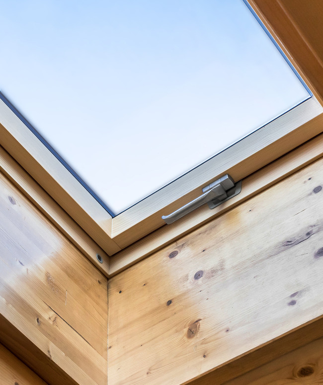Skylight window in wooden house attic. Room with slanted ceiling made of natural eco materials. Environment friendly house.