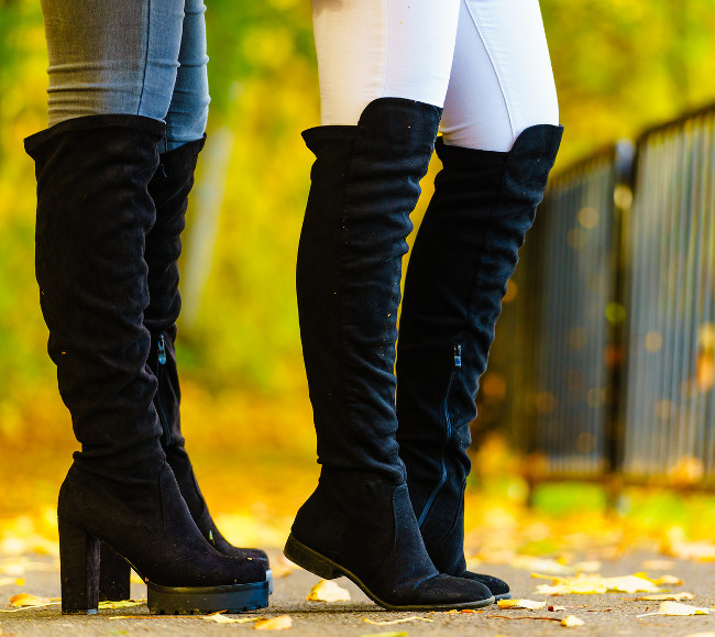 Two unrecognizable women wearing long black heeled knee high boots and jeans. Autumn fashion, warm footwear boots.