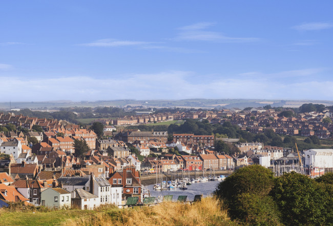 Whitby, North Yorkshire, England - Aug 24, 2019:,UK. Panorama view from a cliff down to the bridge and beyond to the marina, The harbour at Whitby on the North Yorkshire coast, Fishing boats tied up to the quay in Whitby harbour