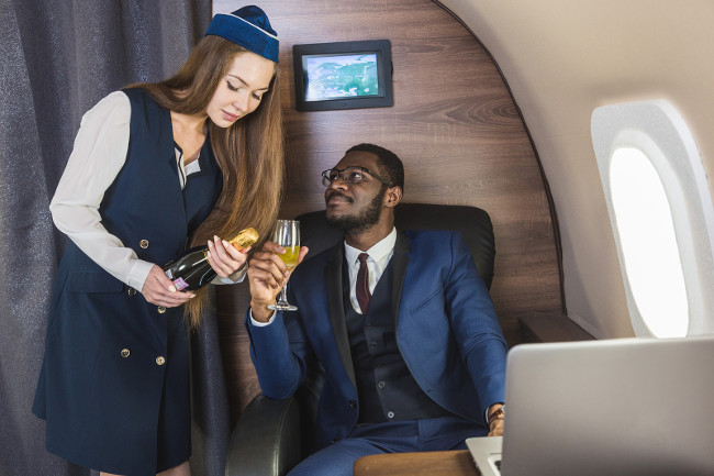 Young successful Afro-American businessman in glasses and a stewardess shows a bottle of wine in the cabin of a private jet. Service and flying first class.