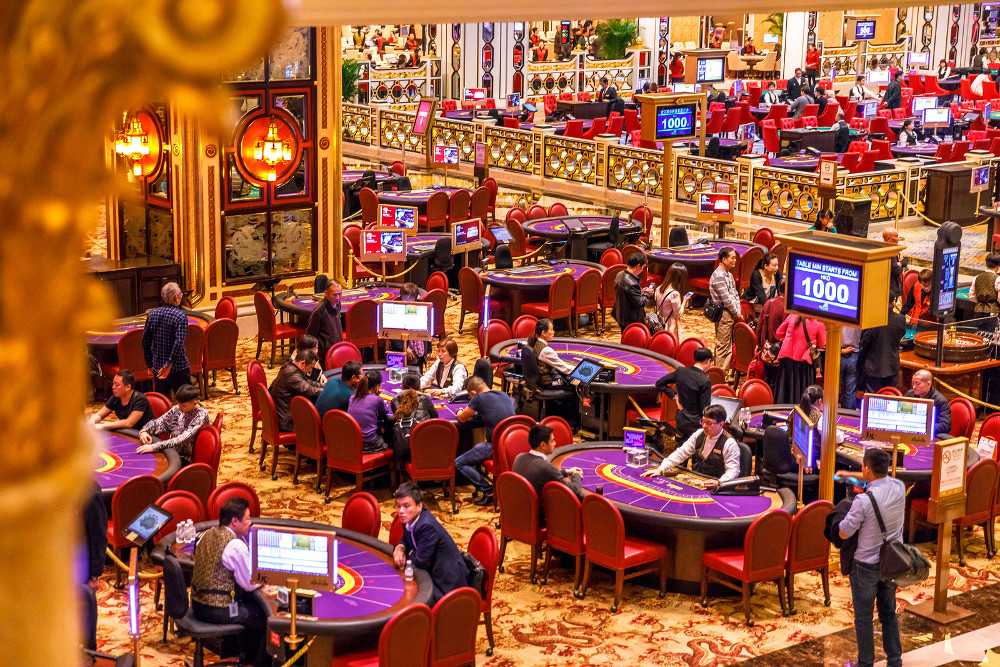 Macau, China - December 9, 2016: Aerial view of blackjack tables and players inside the Venetian Casino in Macau.  Macau is the casino and gambling capital of Asia and, now, the world.
