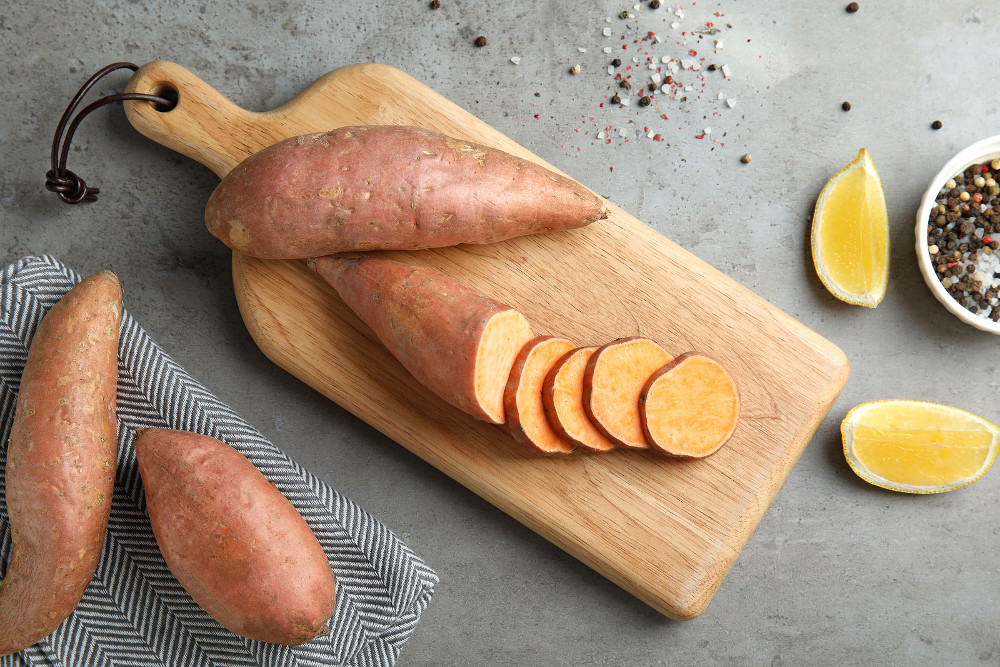 Flat lay composition with sweet potatoes and products on grey background