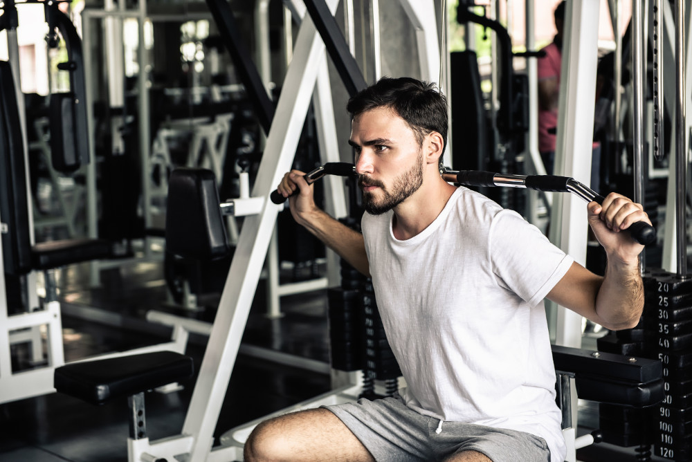 Handsome man is rowing exercise with bodybuilder machine in fitness club.,Portrait of strong man doing working out calories burning in gym., Healthy and fitness sport gym concept.