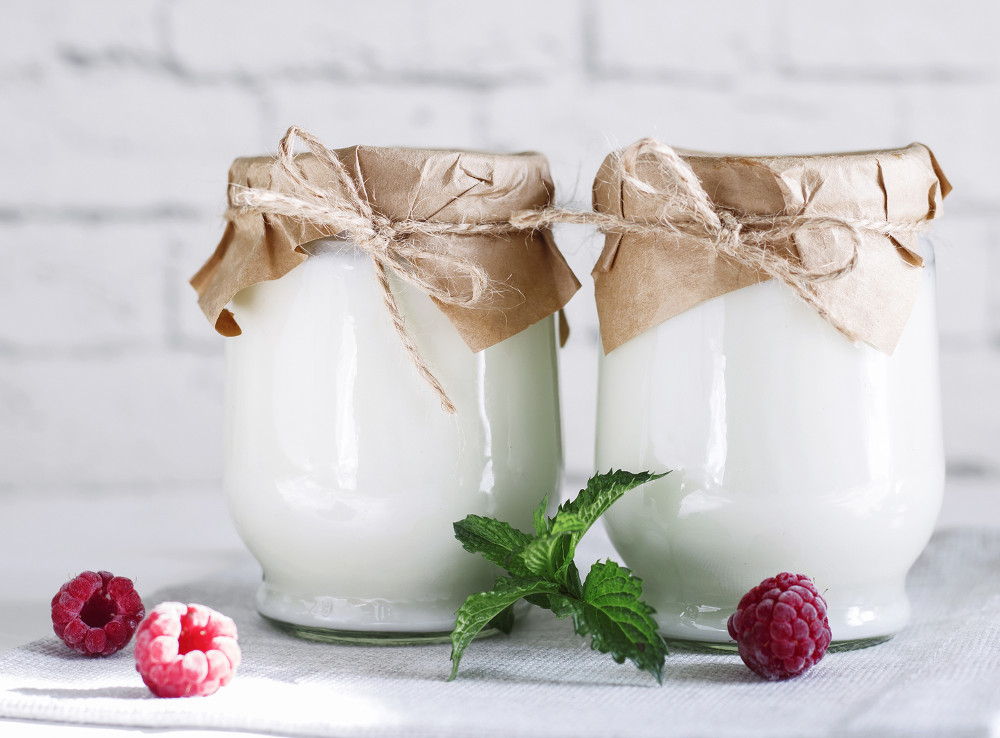 Organic probiotic milk kefir drink or yogurt in glass containers, with raspberry, on the white grey background. Gut health. Probiotic cold fermented dairy drink. Trendy food and drink. Copy space