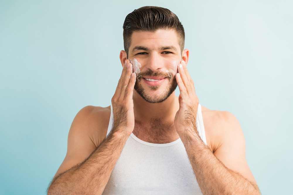 Smiling good looking young Latin male applying anti-aging cream on cheeks while making eye contact against plain background