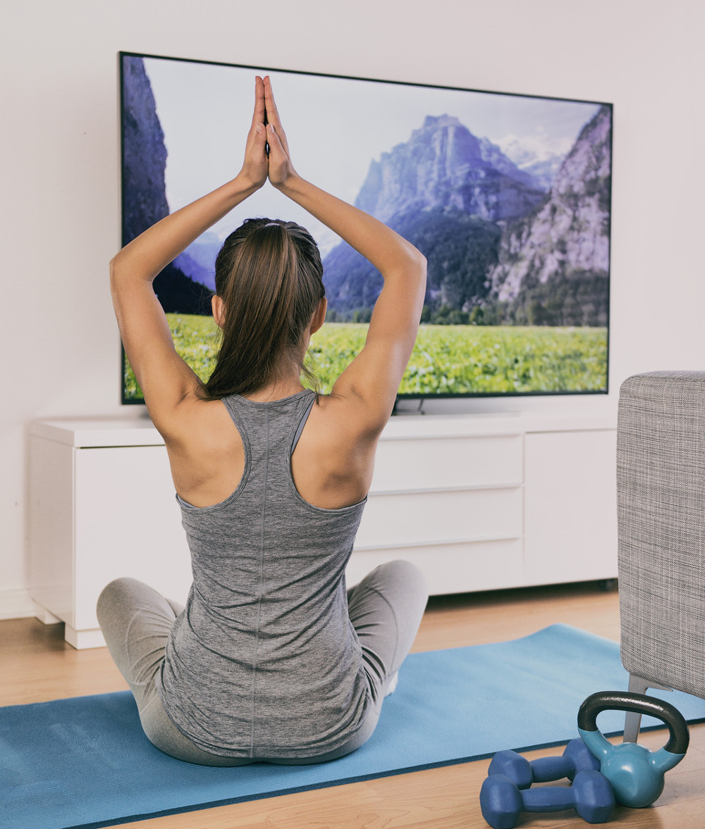 Yoga at home fitness class streaming on TV app online woman training in living room on exercise mat meditating alone - workout lifestyle.