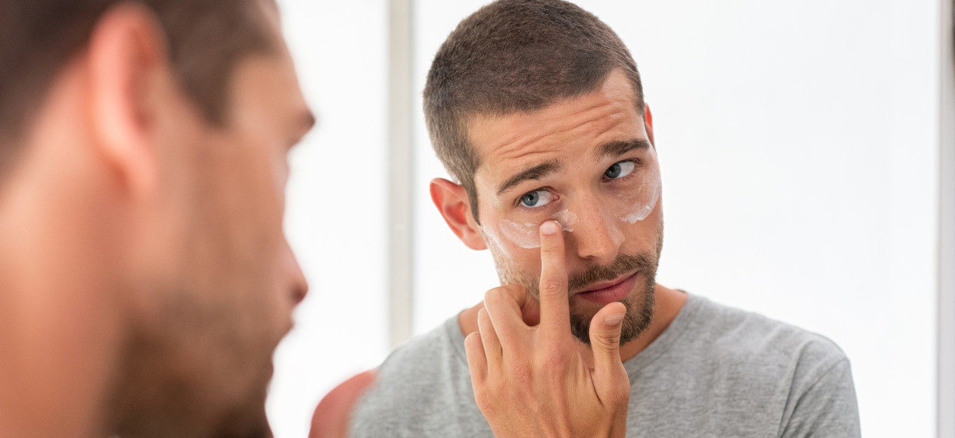 Young man taking care of his undereye wrinkles putting anti aging eye moisturizer. Handsome guy applying moisturizer and looking at himself while standing in front of the mirror in the bathroom.