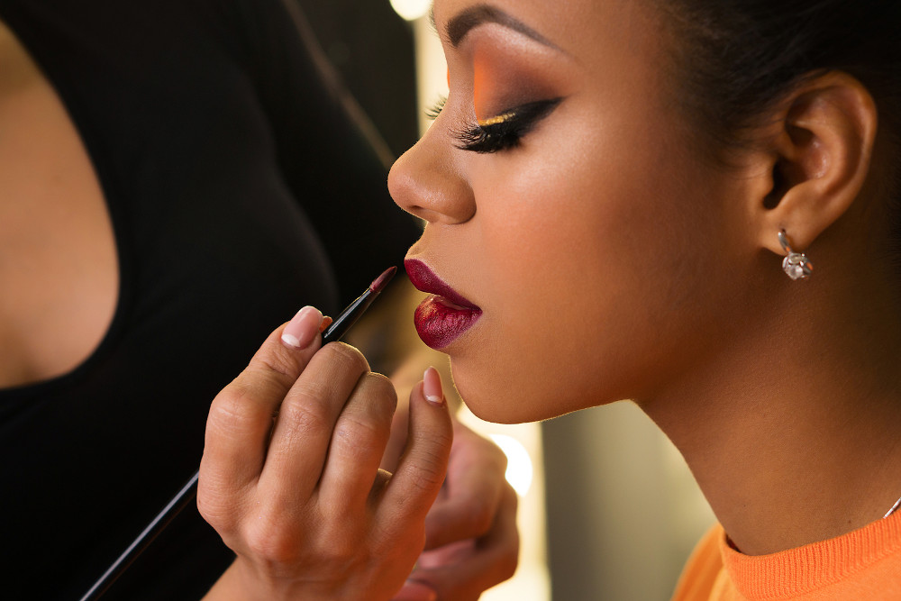 Makeup Artist Working With African American Model In Beauty Salo