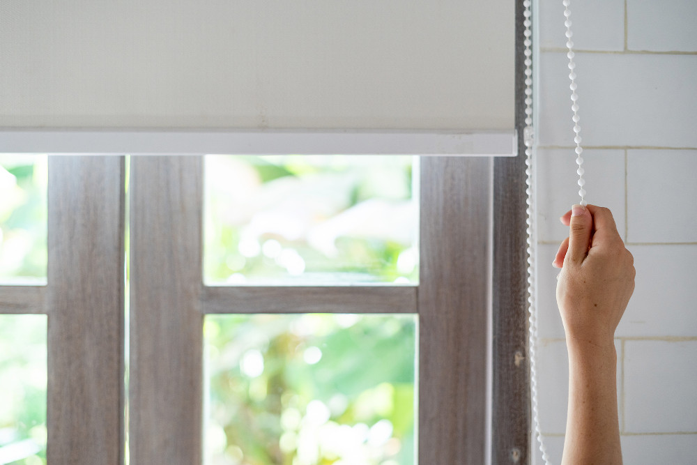 Cropped view of woman pull rope, opened modern white blinds roll on windows in light and tiled bathroom