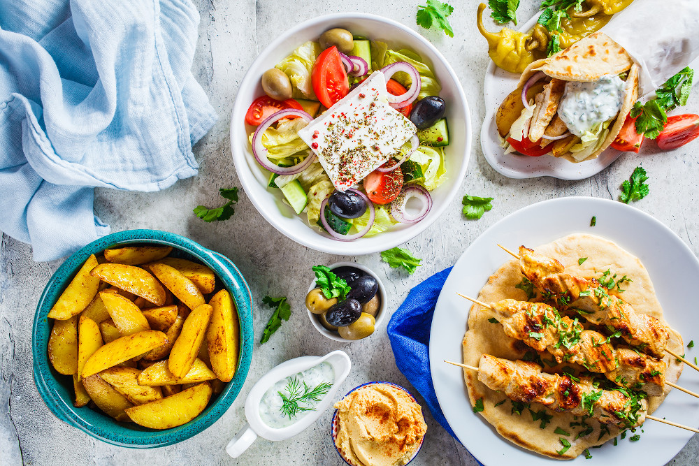 Flat Lay Of Greek Food: Greek Salad, Chicken Souvlaki, Gyro And
