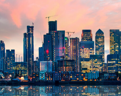 Canary Wharf business and banking area at sunset with beautiful reflection in the River Thames water. London, UK