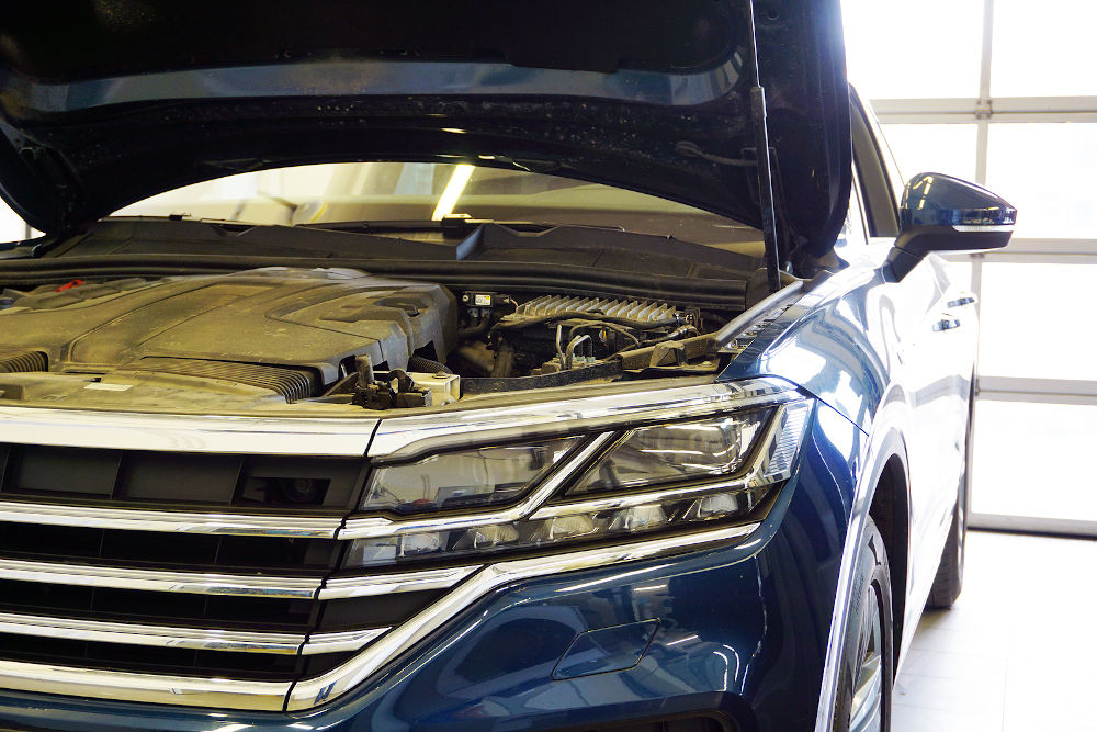 Modern luxury car with an open hood in the service station. In the photo the front of the car, close-up headlight. Service, repair, car diagnostics Concept.