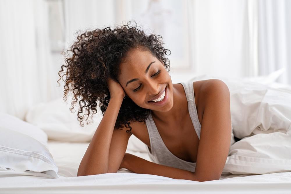 bigstock-Shy-black-girl-lying-on-bed-un-324970981