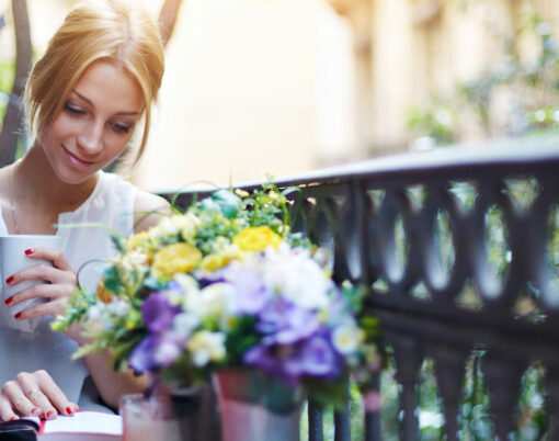 Pretty young woman reading book while sit at terrace table on her balcony, attractive young girl reading book while drinking coffee at sunny day sitting on balcony, sunny morning on beautiful balcony