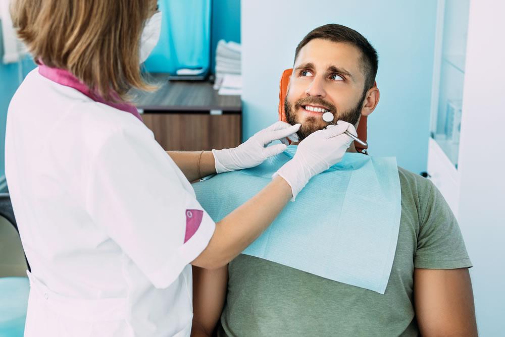 bigstock-A-Man-Treats-His-Teeth-At-The--381797366