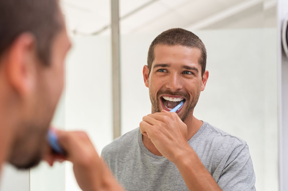 bigstock-Smiling-young-man-with-toothbr-309165322
