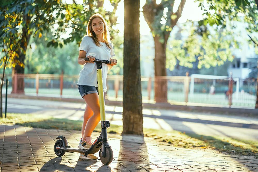 bigstock-Smiling-Woman-Rides-Electric-S-384738083