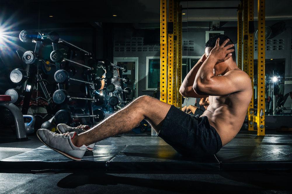 man doing sit ups in gym