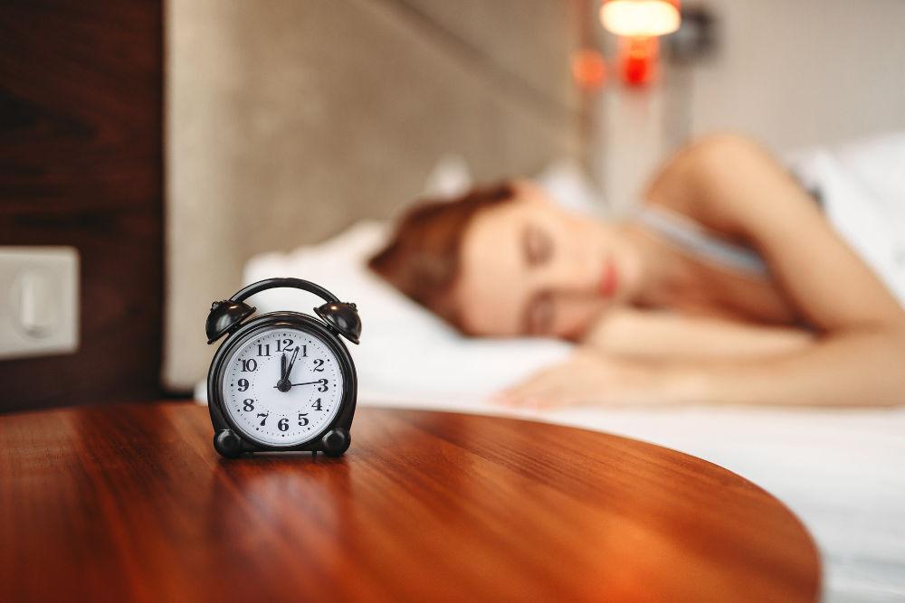 Woman sleeping and an alarm clock on a table