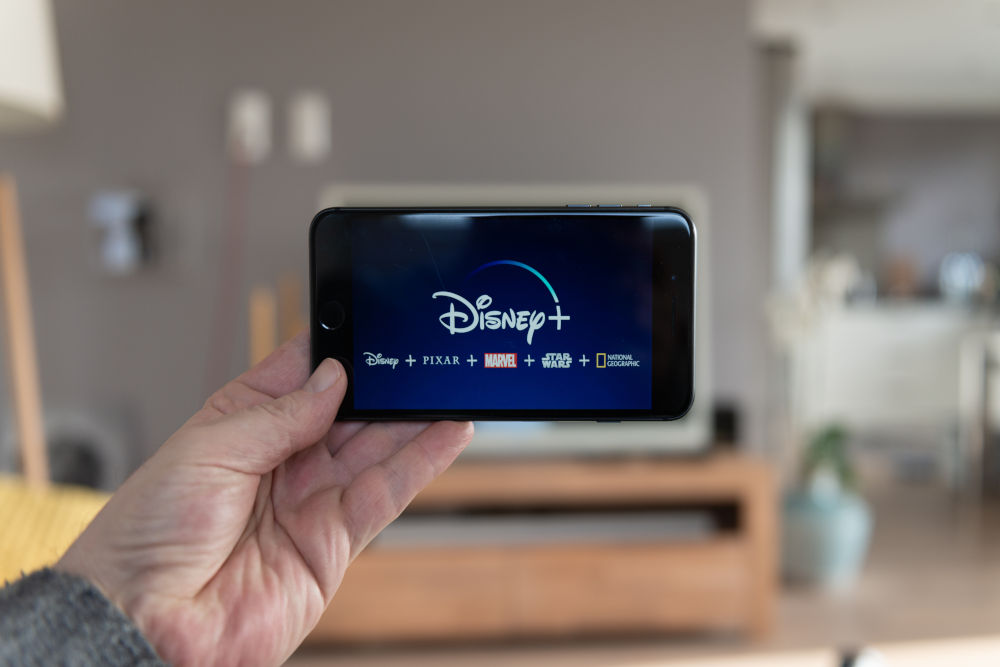 Disney+ on a phone being held by a man