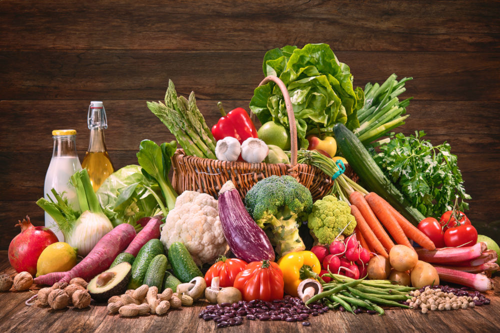 Assortment of fresh organic vegetables and fruits in wicker basket