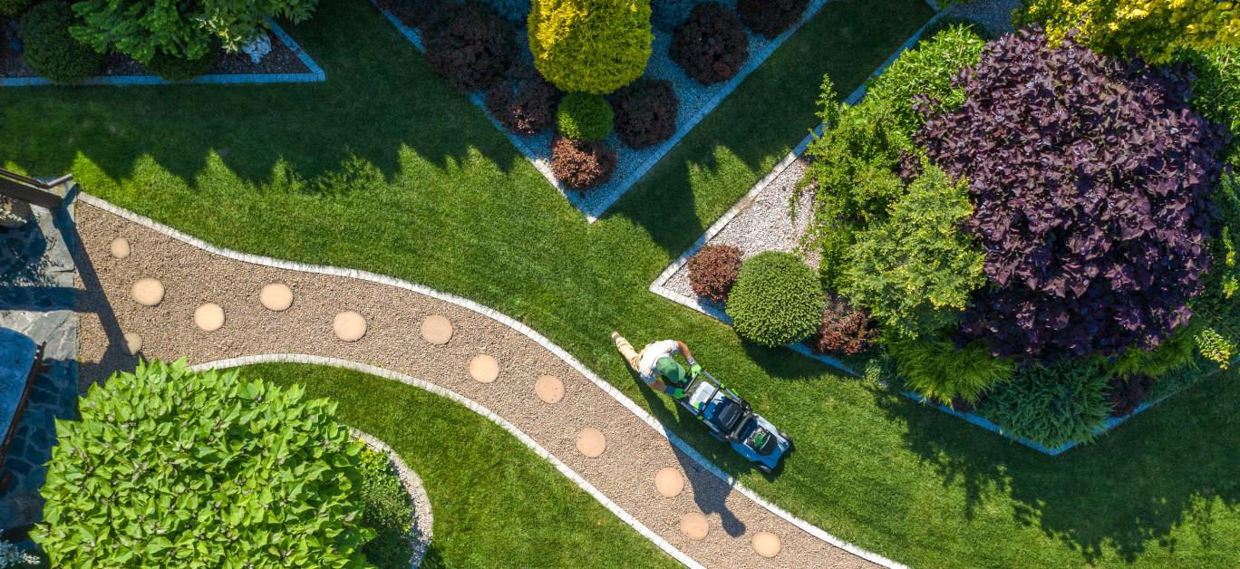 Gardener With Grass Mower Trimming Beautiful Backyard