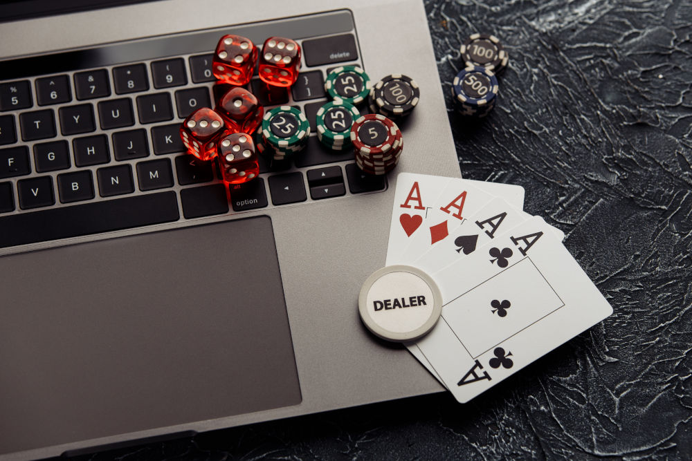 Chips, dices and playing cards on a laptop